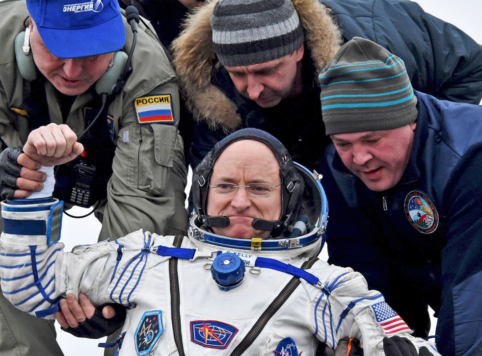 Ground personnel help US astronaut Scott Kelly out of the Soyuz capsule, shortly after it landed near the town of Jezkazgan in Kazakhstan, yesterday. Commander Kelly was immediately put through a number of physical tests