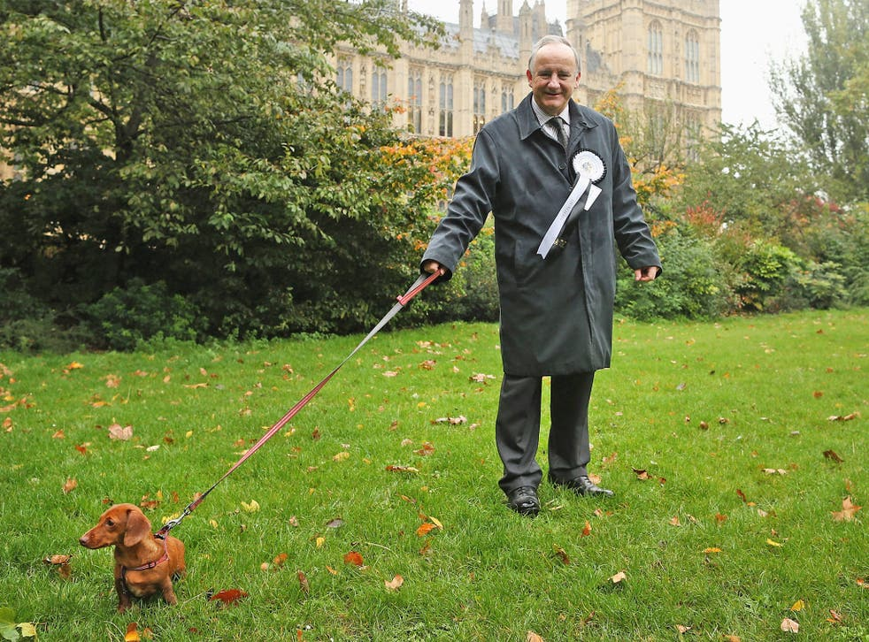 Laurence Robertson, Conservative MP for Tewkesbury stands in front of The Houses of Parliament with his dog, Sausage