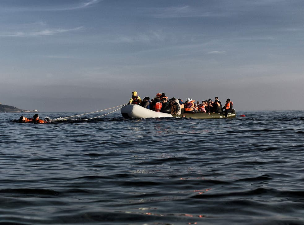 Migrants arrive on a rubber boat in Mytilene, on the Greek island of Lesbos, after crossing the Aegean sea from Turkey
