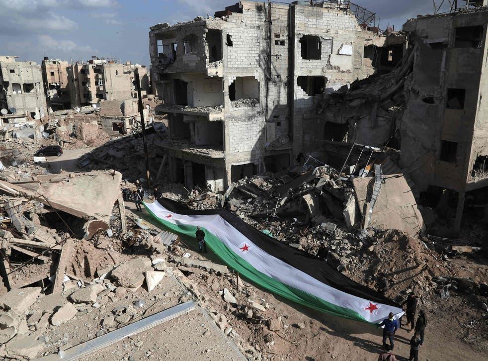 Activists hold a pre-Assad Syrian flag in Jabar, Damascus