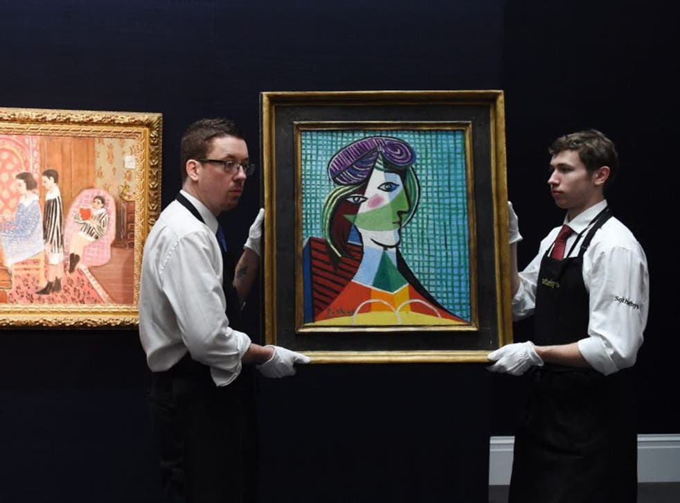 Staff members carry the painting 'Tete de Femme (1935)' by Spanish artist Pablo Piccaso next to French artist Henri Matisse's work 'La Lecon de Piano' during a press preview at Sotheby's auction house in London