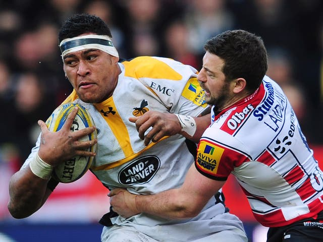 Nathan Hughes of Wasps is tackled by Greig Laidlaw of Gloucester