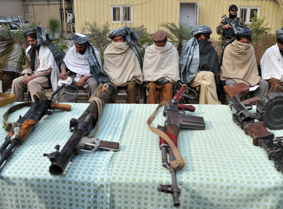 Former Taliban fighters sit alongside their weapons, prior to handing them over at a ceremony in Jalalabad in 2014