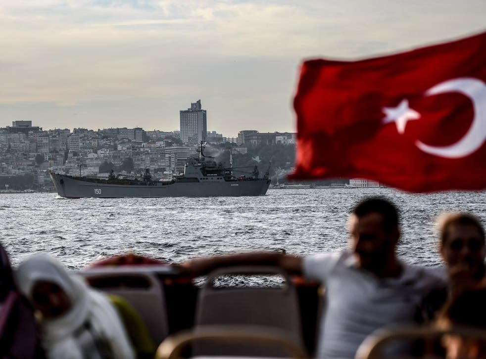 A Turkish flag flies from an Istanbul ferry as a Russian warship sails through the Bosphorus en route to the Mediterranean