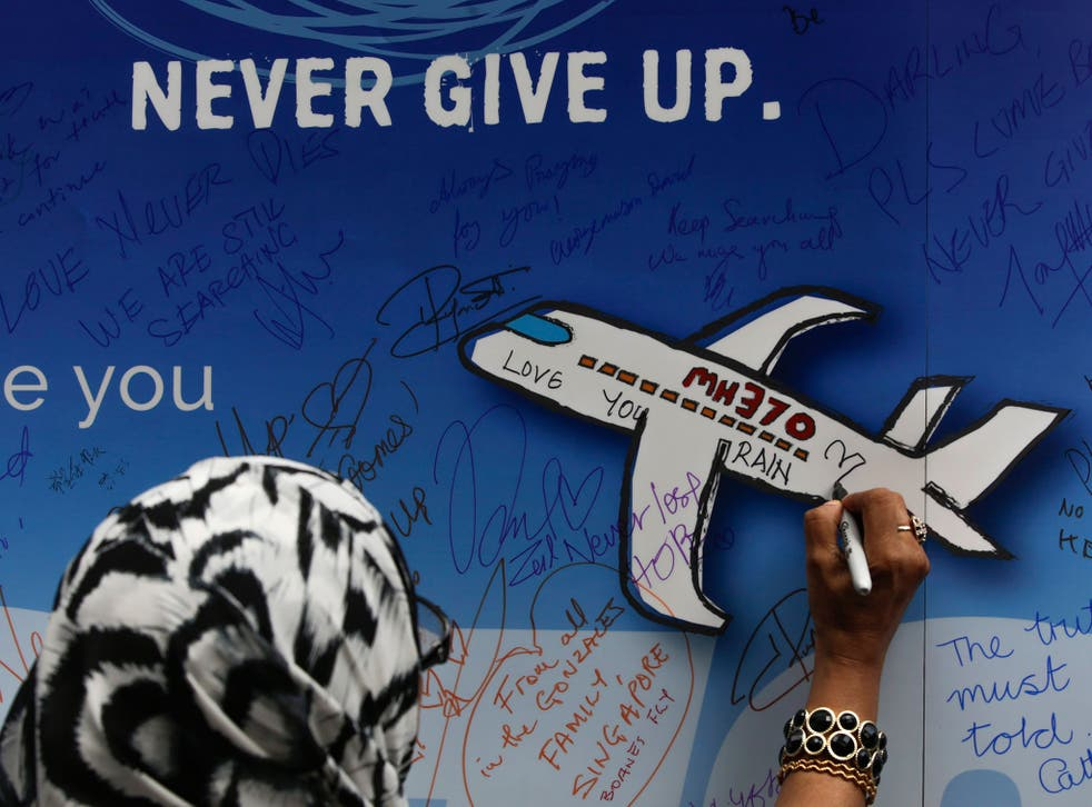 A woman writes messages for the passengers of flight MH370 on a banner during a remembrance ceremony to mark the second anniversary of the plane's disappearance in Kuala Lumpur