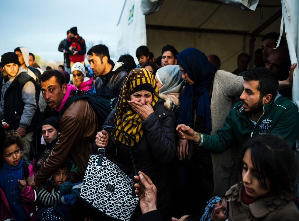 A woman reacts after losing sight of her child near the gate at the Greek-Macedonian border