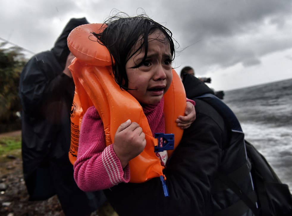 Refugees and migrants arrive at Lesbos island after crossing the Aegean sea from Turkey on 23 October 2015