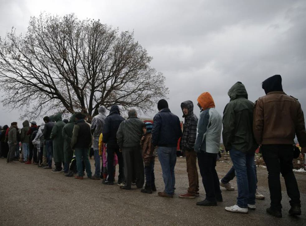 Migrant men queue for food at a makeshift camp near the village of Idomeni, Greece, as they wait to cross the Greek-Macedonian border