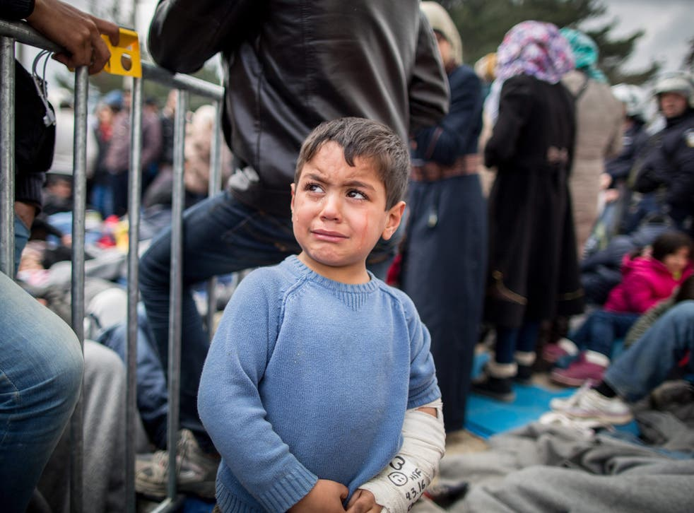 A refugee boy cries in front of the border gate in the refugee camp at the Greek-Macedonian border near Idomeni, Greece