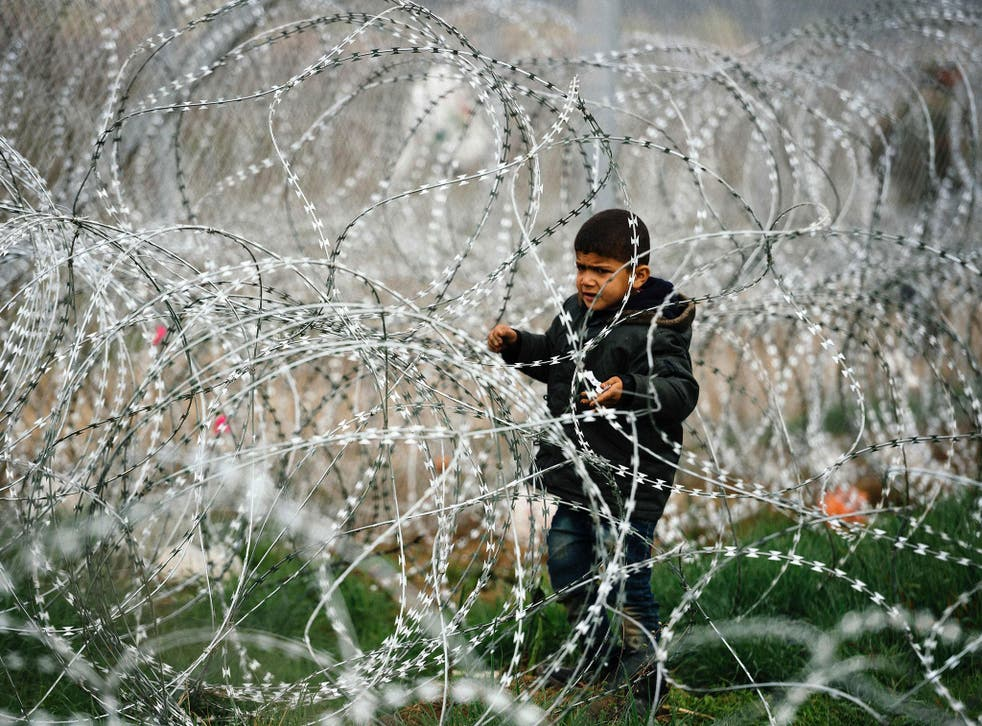 A child stands among a razor-topped fence close to the gate at the Greek-Macedonian border, 7 March 2016