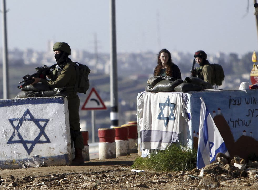 Israeli soldiers stand guard at Gush Etzion junction in the West Bank Friday, March 4, 2016, after a Palestinian woman allegedly tried to run over a soldier with her car.