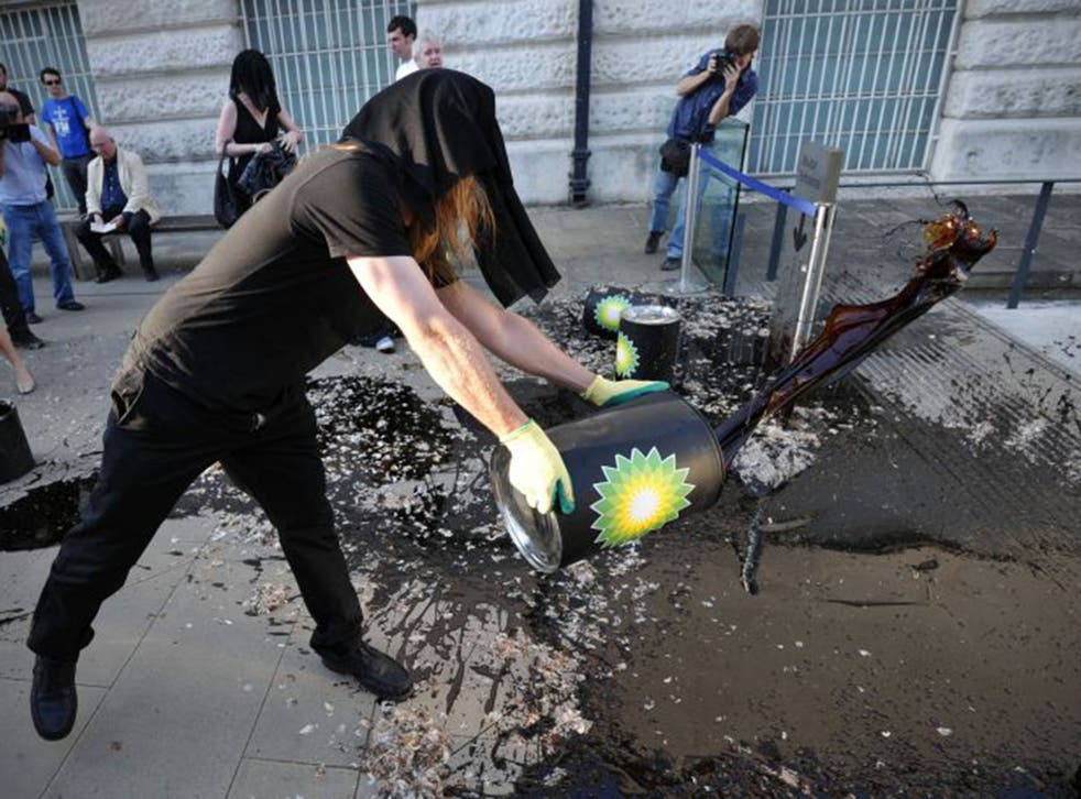 A protester dumps oil-like molasses at Tate Britain in 2010