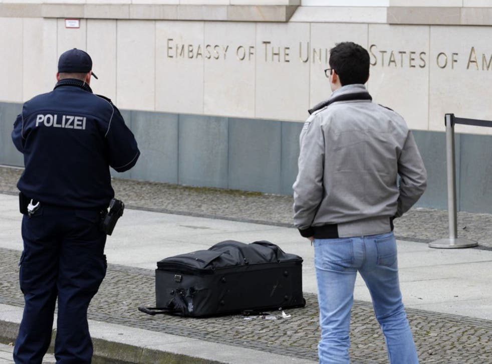 Police officers photograph a suitcase in front of the US embassy in Berlin, Germany, Friday, March 11, 2016.