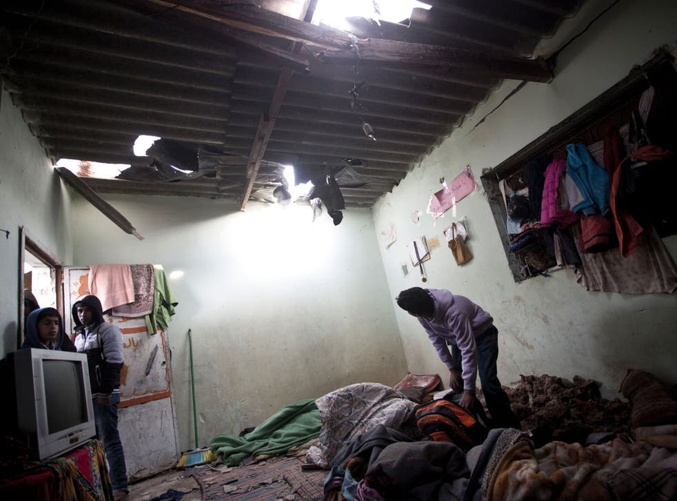 A Palestinian boy inspects a bedroom of the damaged Khoussa family home after an Israeli strike on Hamas bases in Beit Lahiya, northern Gaza strip