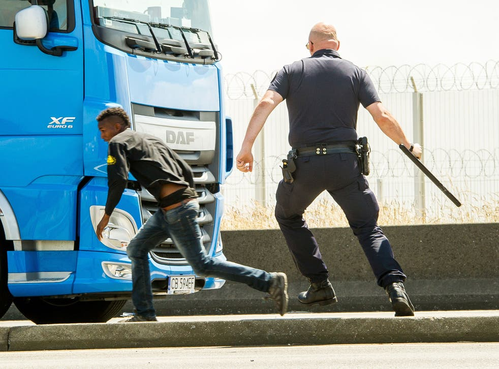 French police (CRS) officer runs after a migrant trying to hide in a lorry heading for England in Calais on June 17, 2015.