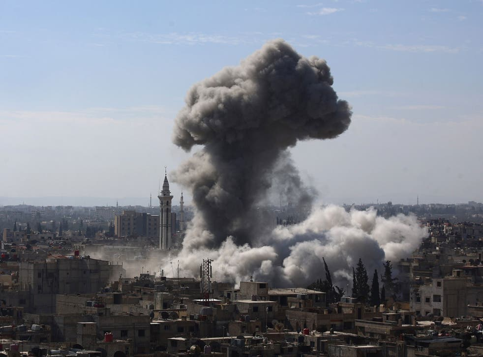 A cloud of smoke rises following an air strike by Syrian government forces in the rebel-held area of Douma, north east of the capital Damascus