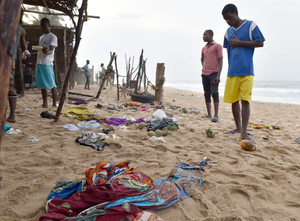 Locals look at the belongings left behind by people who fled the gunman in Grand Bassam