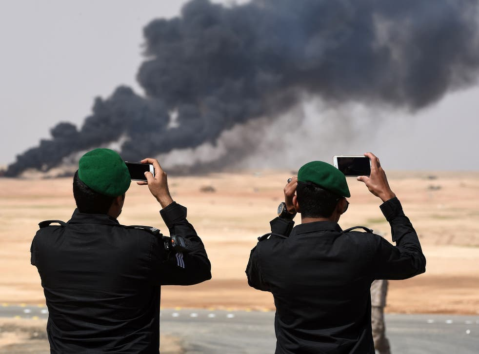 Saudi officers take photos of a joint military exercise between 21 Muslim nations in the Saudi desert