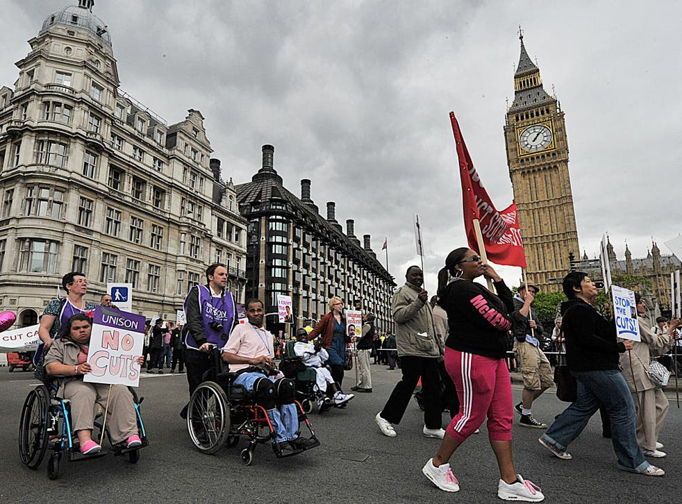 Disability rights protestors demonstrate past the Houses of Parliament, in central London