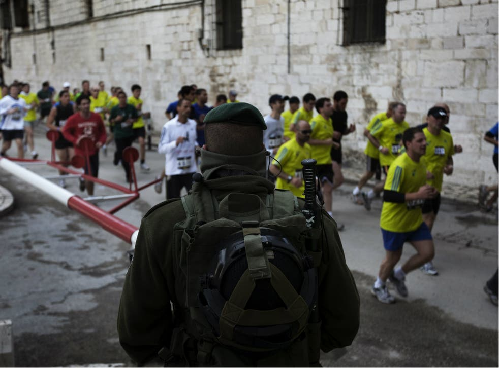 Israeli forces keep watch as foreigners and Israelis run through Jerusalem's Old City during Jerusalem's first-ever marathon on March 25, 2011