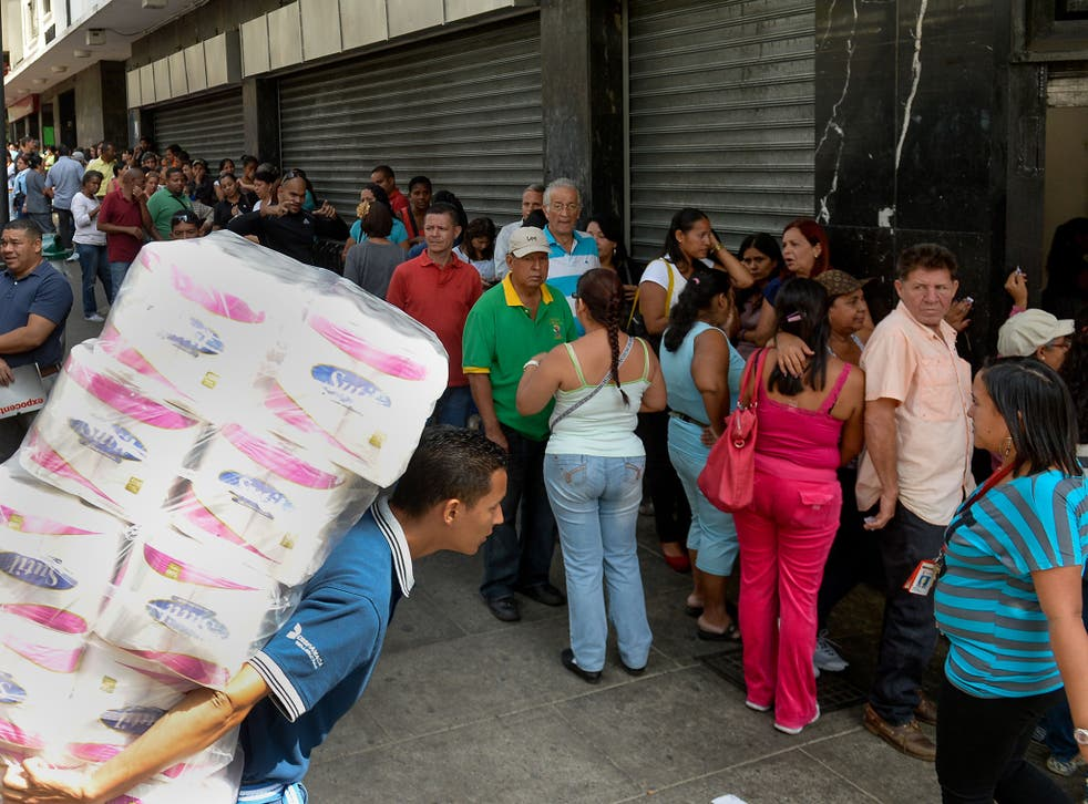 Shoppers in Caracas queue outside a store. In addition to an energy crisis, Venezuela has experienced food shortages and price hikes