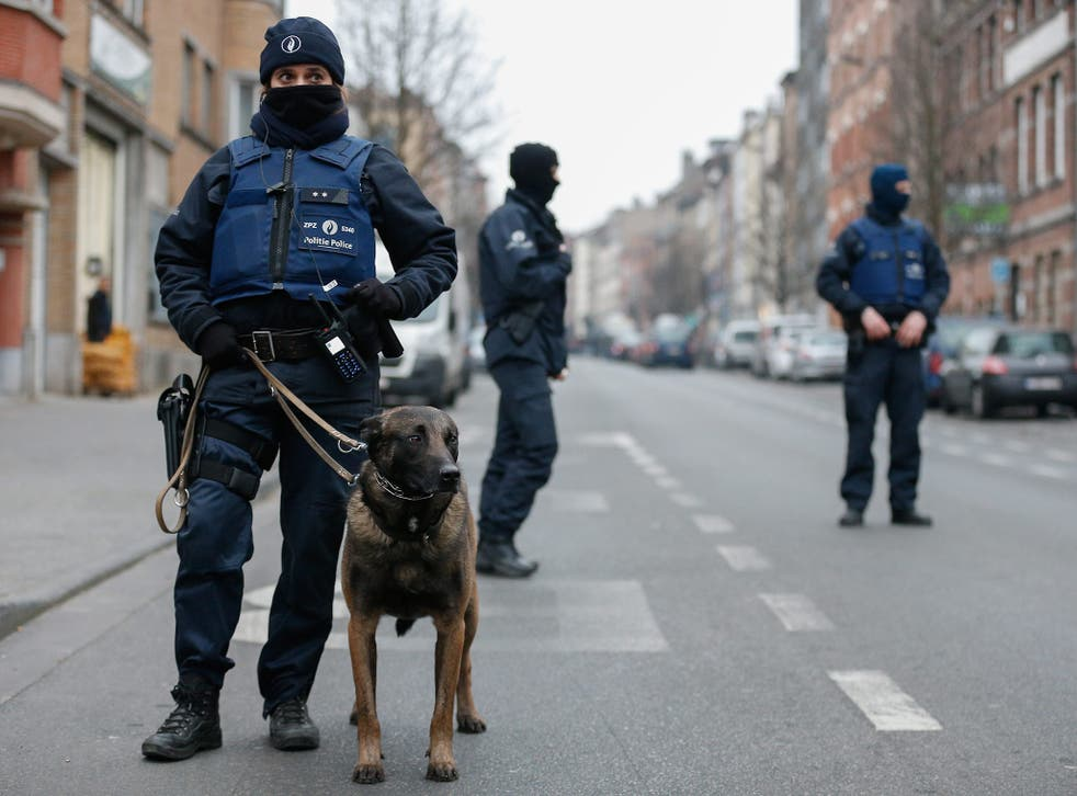 A Belgian police's dog handler helps to seal off the area during the anti-terror operation
