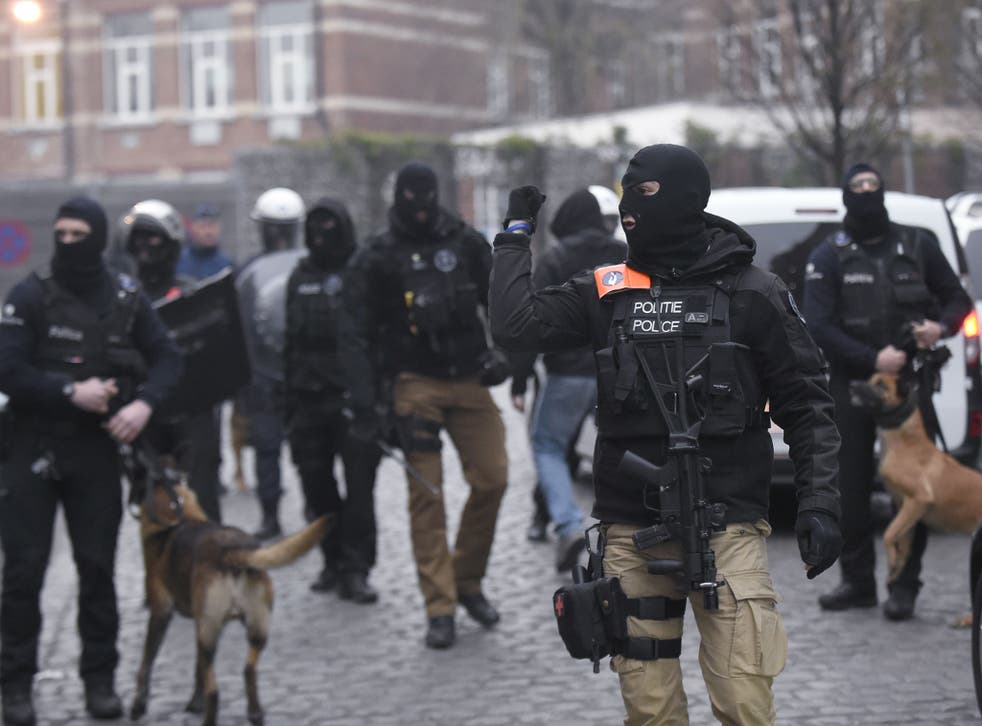 Belgian policemen walk in a street during a police action in the Molenbeek-Saint-Jean district in Brussels,
