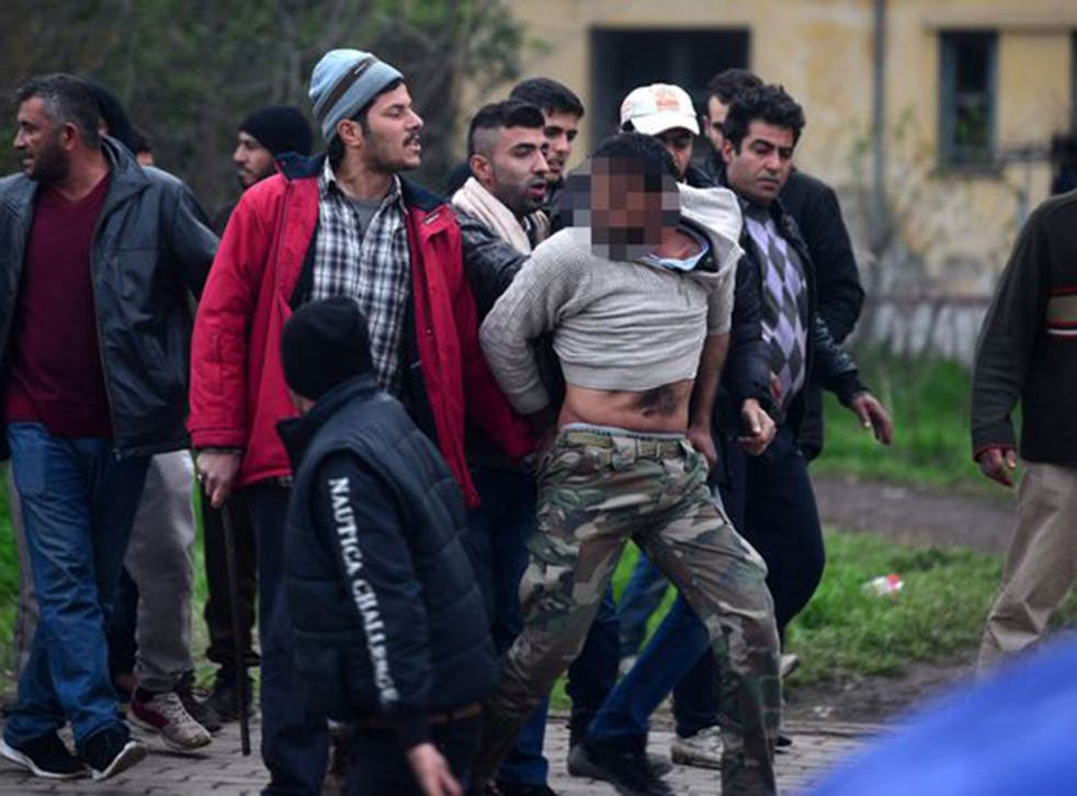 The men were pictured leading the alleged paedophile a mile through the camp, while other refugees tried to hit him