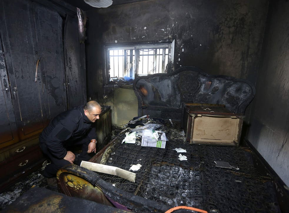 A Palestinian police member inspects the damage inside a burnt-out house belonging to a key witness to an arson attack