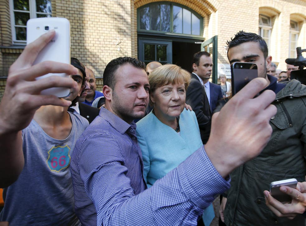 Migrants from Syria and Iraq take selfies with German Chancellor Angela Merkel outside a refugee camp near the Federal Office for Migration and Refugees after their registration at Berlin's Spandau district, Germany