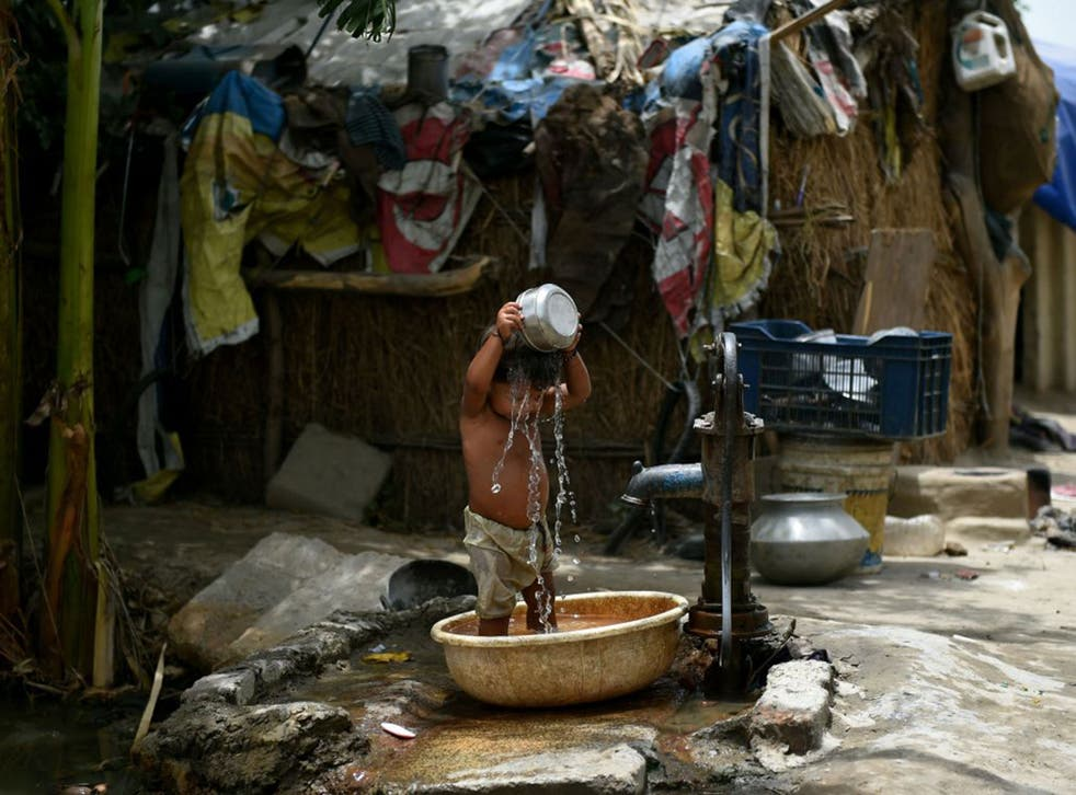 A young Indian boy attempts to cool himself off in Delhi