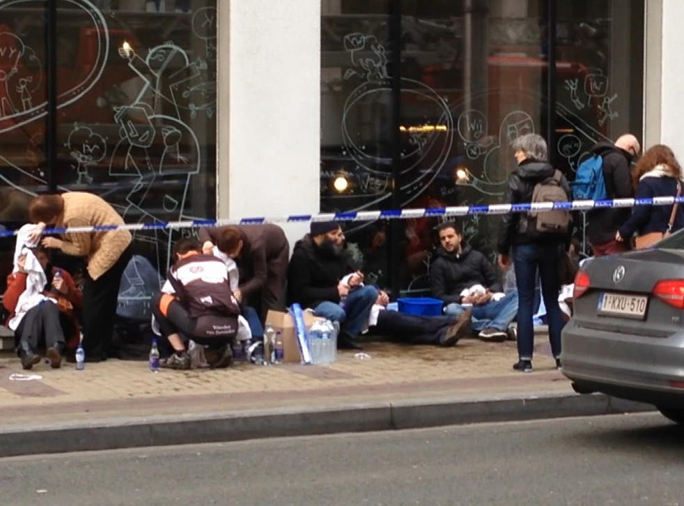 Wounded victims are treated outside the Brussels metro station after a bomb exploded on Tuesday morning.