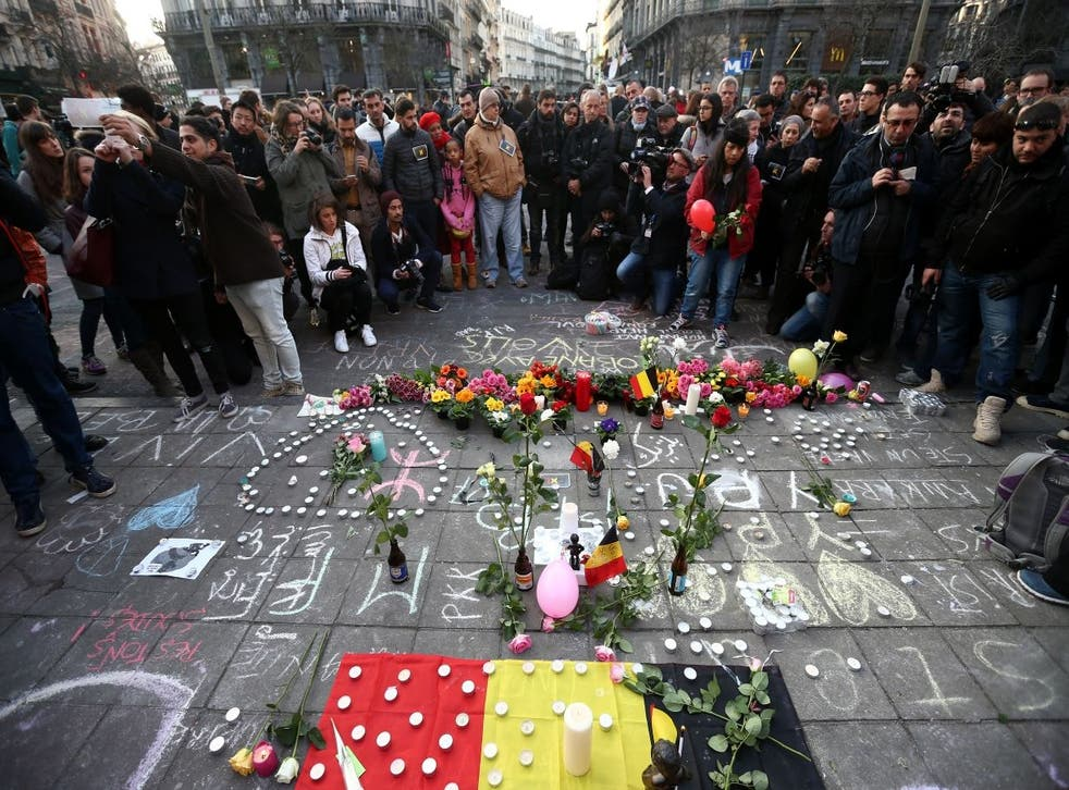 People gather to leave tributes at the Place de la Bourse following today's attacks on March 22, 2016 in Brussels, Belgium
