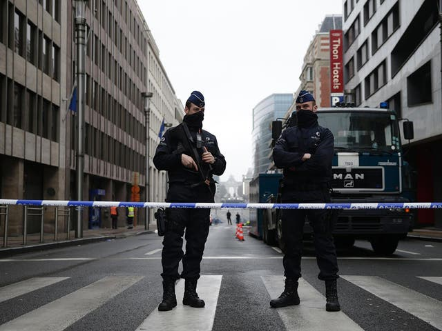Belgian police officers stand guard near Maalbeek subway station in Brussels on 23 March