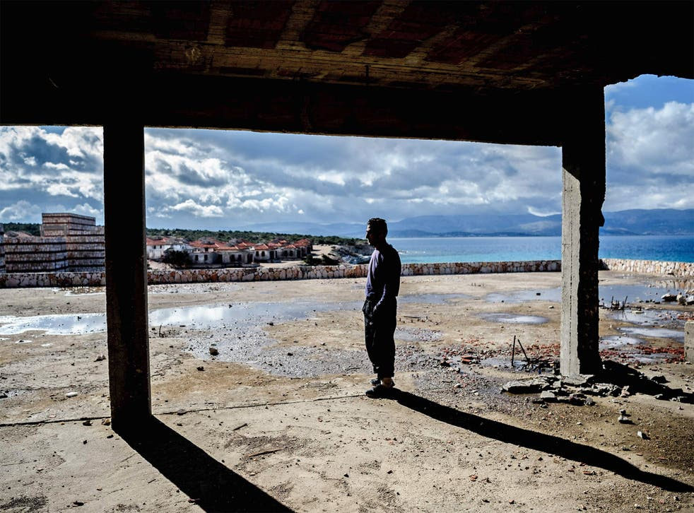 A man waits inside an abandoned house to cross to the island of Chios in Cesme, Greece. Aid organistaions are refusing to support a former registration centre on Chios as it has now become a refugee detention centre