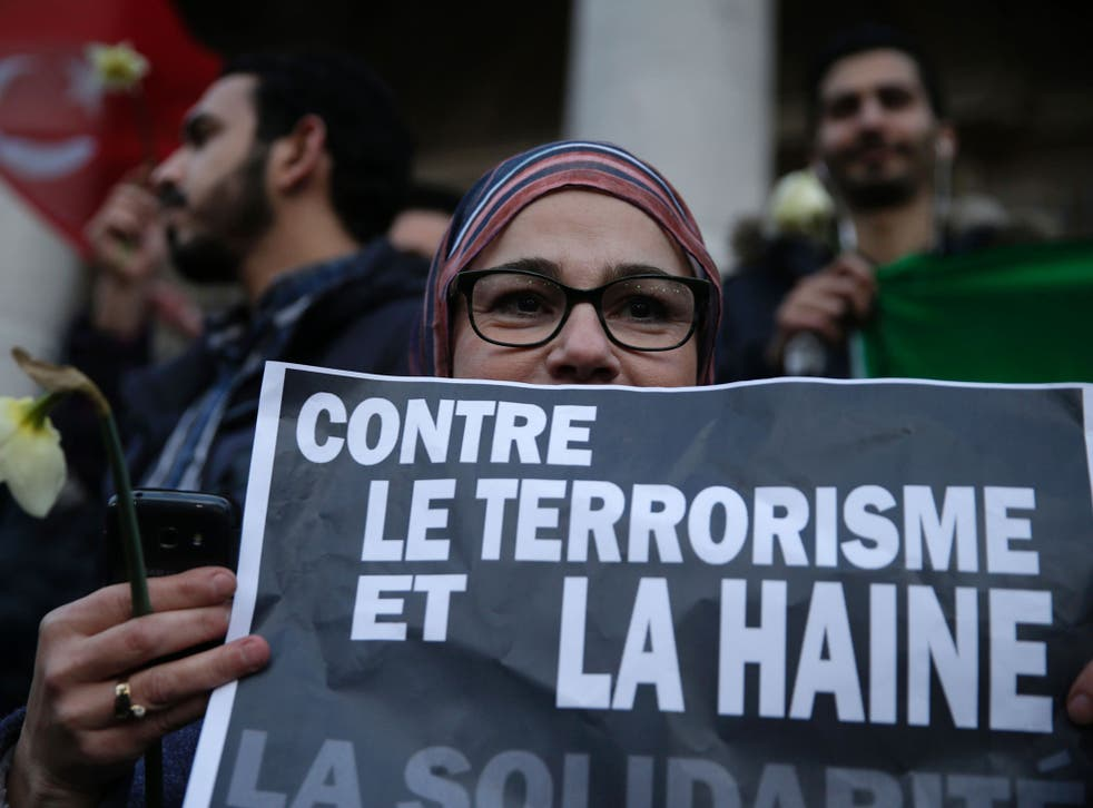 A woman holds a placard reading 'Against terrorism and hatred, Solidarity', at a makeshift memorial on the Place de la Bourse in Brussels. Responsibility for the attack has been claimed by Isis