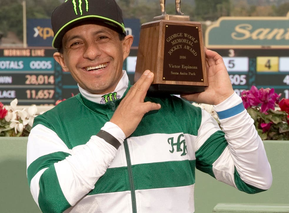 Triple Crown champion jockey Victor Espinoza, a 43-year-old native of Mexico City, poses for a photo with his trophy he received in a winnerís circle ceremony at Santa Anita Park, Arcadia, Calif.