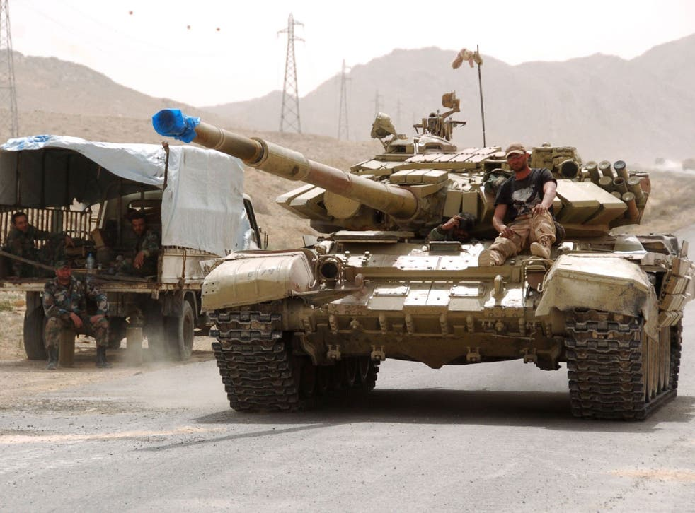 Syrian pro-government forces drive a tank on the outskirts of Palmyra during a military operation to retake the ancient city from Isis