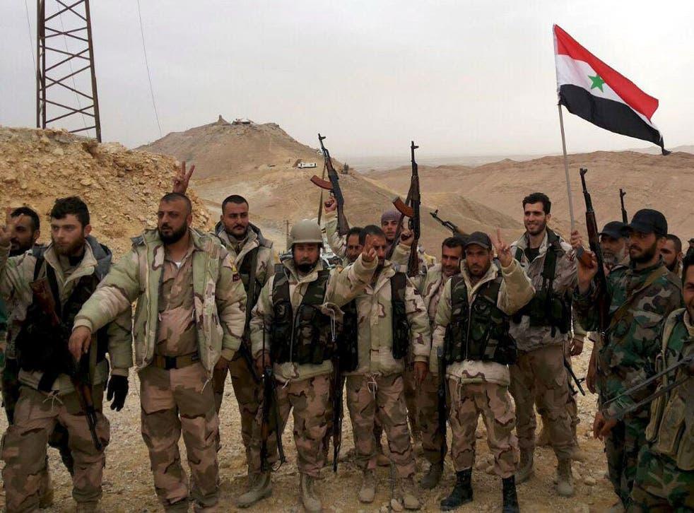 Troops loyal to Bashar al-Assad celebrate on the edge of Palmyra