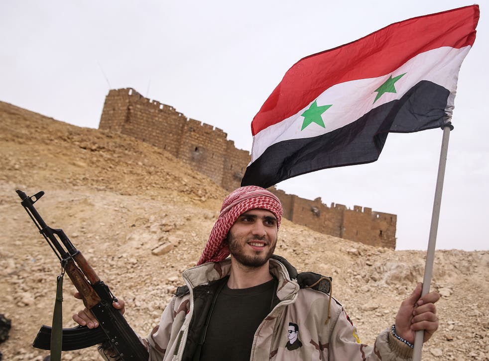 A Syrian soldier celebrates on the outskirts of Palmyra