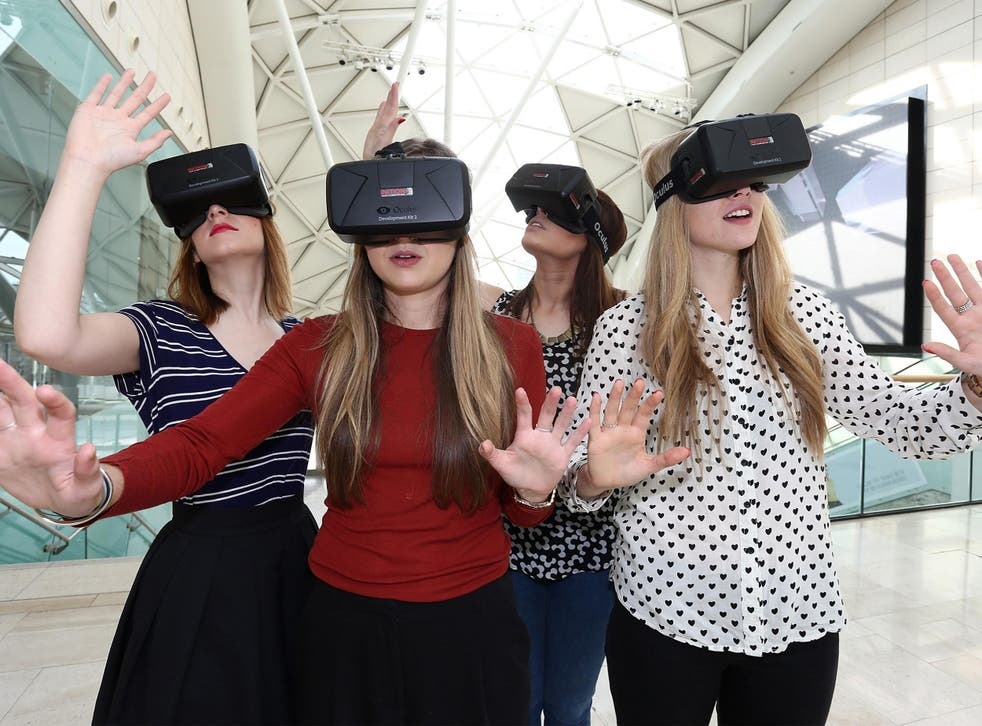 Women use the Oculus Rift DK2 at the Westfield Shopping Centre in London