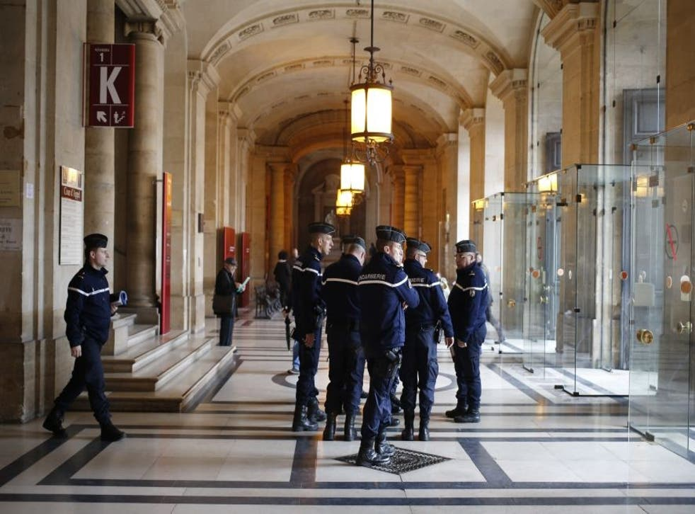 French gendarmes patrol in the Paris hall of Justice while Reda Kriket is being questioned by a magistrate who then filed preliminary terror charges