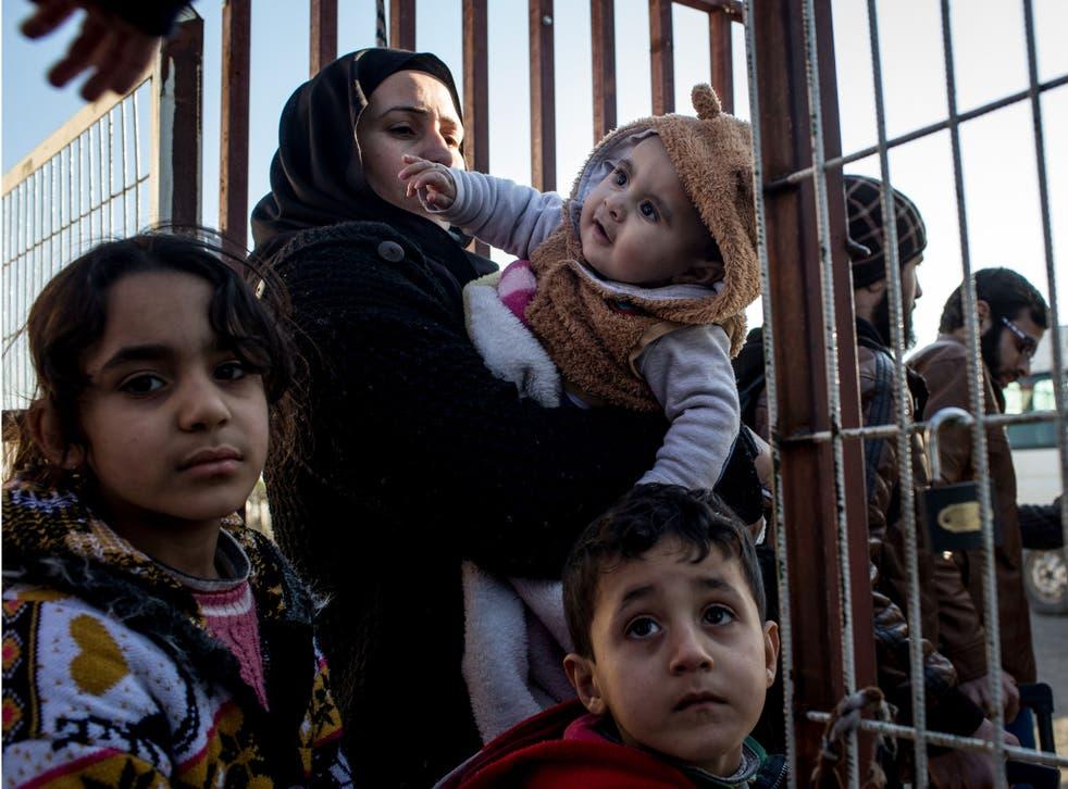 Migrants wait at the Syria-Turkey border