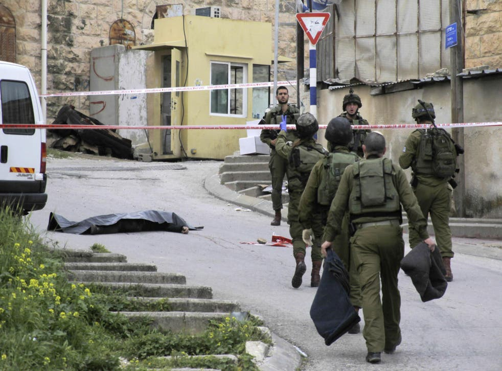 Israeli soldiers attend the body of Abed al-Fatah al-Sharif, who was shot and killed while lying wounded in Hebron