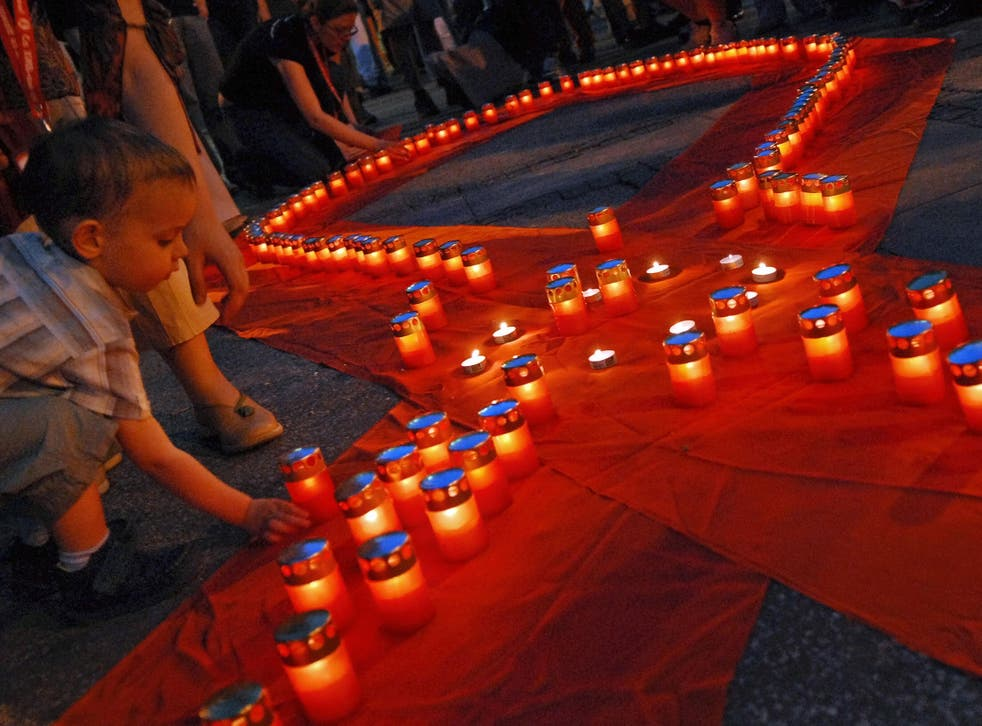 A young boy lights a candle at an AIDS memorial service in Belgrade, Serbia