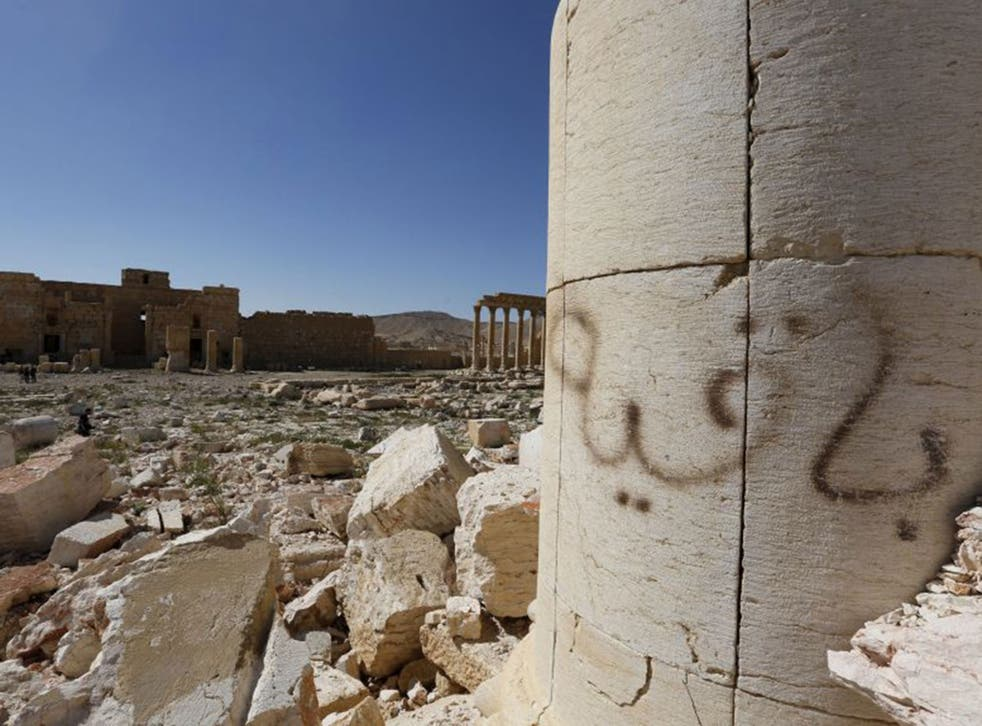 """Graffiti sprayed by Islamic State militants which reads """"We remain"""" is seen at theTemple of Bel in historic city of Palmyra."""