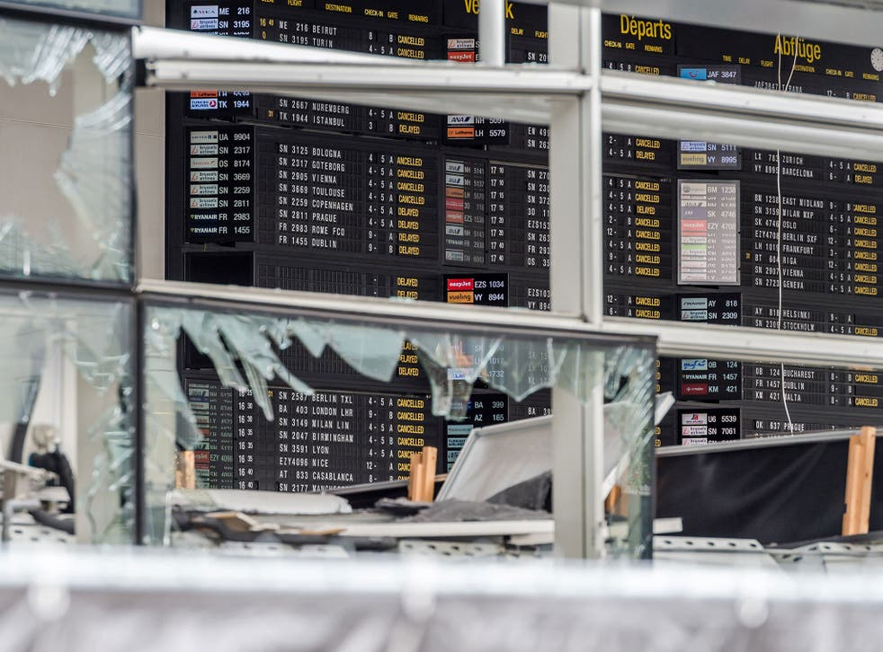 An arrivals and departure board is seen behind blown out windows at Zaventem Airport in Brussels on 23 March
