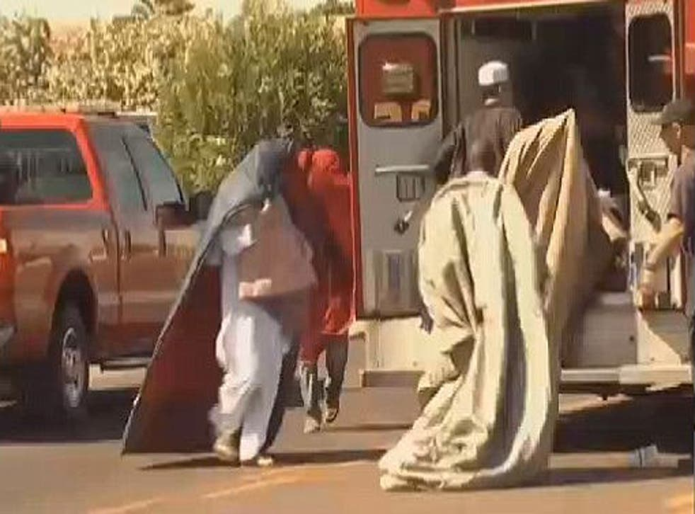 Men rushed to the ambulance with blankets covering their heads