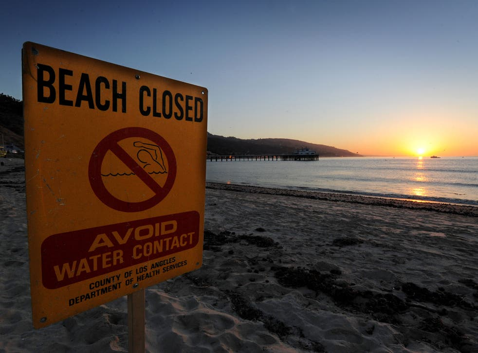 A beach closed sign warns against contaminated water