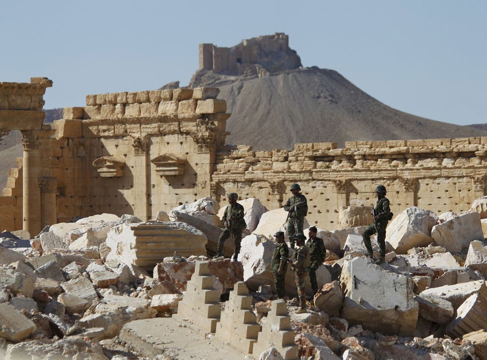 Syrian army soldiers in the ruins of the temple of Bel in Palmyra, which was retaken from Isis